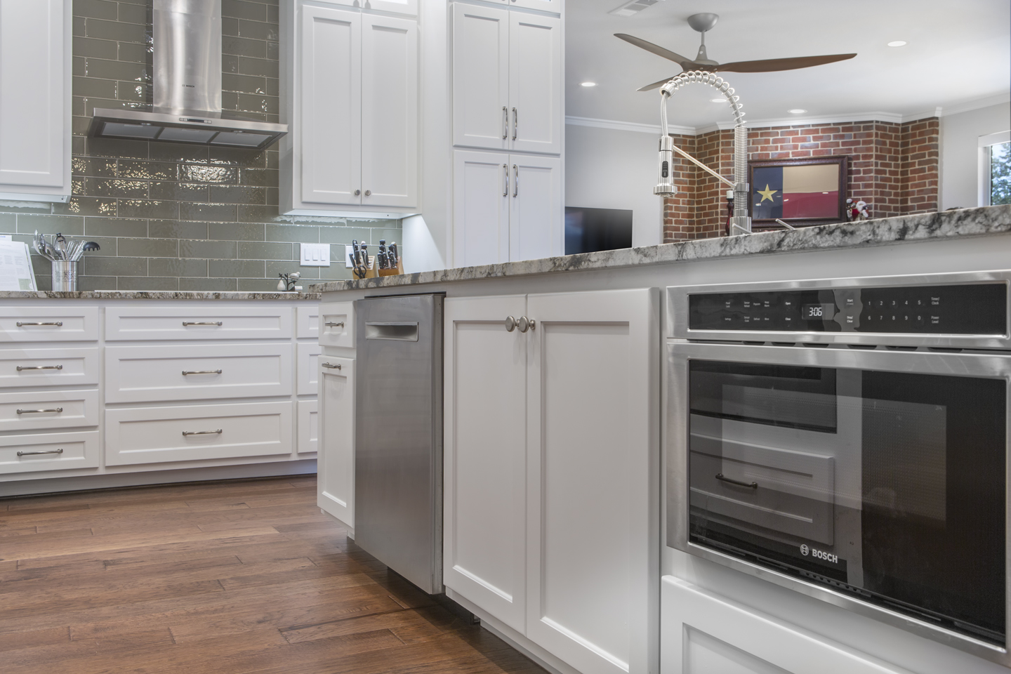 angled shot of kitchen island showcasing under counter microwave drawer, dishwasher, and pull-out trash bin.